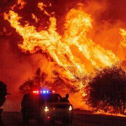 Un oficial de la ley observa cómo las llamas se lanzan al aire mientras el fuego continúa propagándose en el incendio Bear en Oroville, California. | Foto:JOSH EDELSON / AFP