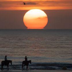 Los jinetes y sus caballos caminan por la arena mientras el sol se pone en la playa de Deauville, noroeste de Francia, durante el 46 ° festival de cine estadounidense de Deauville. | Foto:Loic Venance / AFP