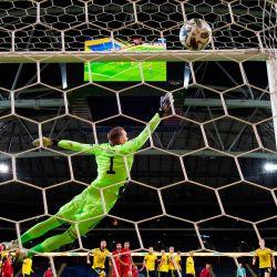 El delantero portugués Cristiano Ronaldo anota un tiro libre sobre el portero sueco Robin Olsen, su gol número 100 para Portugal, durante el partido de fútbol de la UEFA Nations League entre Suecia y Portugal en Solna, Suecia. | Foto:Jonathan Nackstrand / AFP