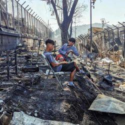 Los migrantes se sientan dentro del campamento Moria quemado en la isla griega de Lesbos, después de un gran incendio. | Foto:Anthi Pazianou / AFP