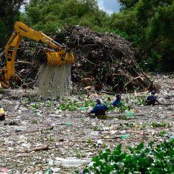 Trabajadores de la Autoridad del Lago Amatitlán (AMSA), recolectan basura arrastrada por las lluvias y retenida por una barrera flotante instalada en uno de los afluentes del Lago en Amatitlán, 30 kms al sur de la Ciudad de Guatemala, en medio del Covid- 19 pandemia de coronavirus. | Foto:Johan Ordonez / AFP