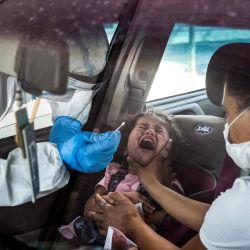 Una niña reacciona mientras se somete a una prueba de muestra de hisopo para la enfermedad del coronavirus COVID-19 por un miembro del servicio médico de emergencia nacional Magen David Adom (Escudo Rojo de David), en una estación de pruebas en el este de Jerusalén. | Foto:Emmanuel Dunand / AFP