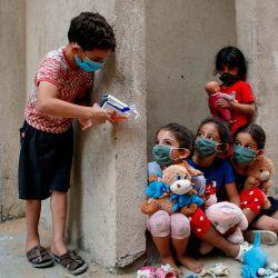 Niños palestinos, vestidos con máscaras debido a la pandemia del coronavirus Covid-19, juegan afuera de su casa en la ciudad de Gaza. | Foto:MOHAMMED ABED / AFP