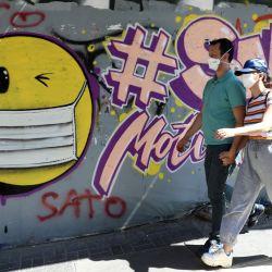 Personas que usan mascarillas pasan junto a un grafito que representa una cara sonriente con una mascarilla en Ankara, en medio de la pandemia de Covid-19, causada por el nuevo coronavirus. | Foto:Adem Altan / AFP