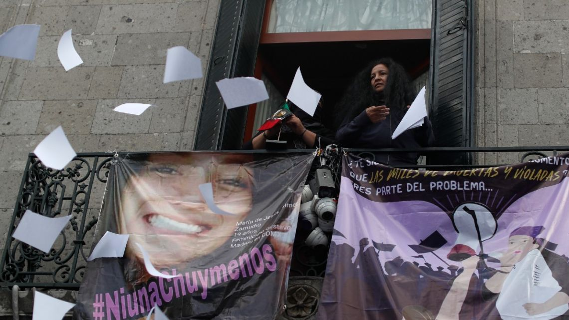 Gender violence activist Yesenia Zamudio, standing beside an image of her 19-year-old daughter who was killed in 2016 in a suspected femicide, throws office supplies out a window at the National Human Rights Commission office, which protesters have been occupying since last week in Mexico City, Tuesday, September 8, 2020.