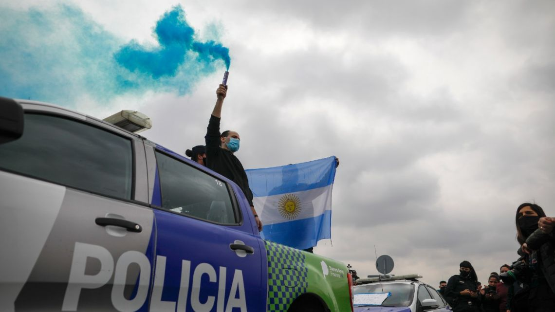 A policeman holds up a flare during a protest in which provincial police are demanding improved wages and working conditions amid the new coronavirus pandemic in La Matanza, Wednesday, September 9, 2020.