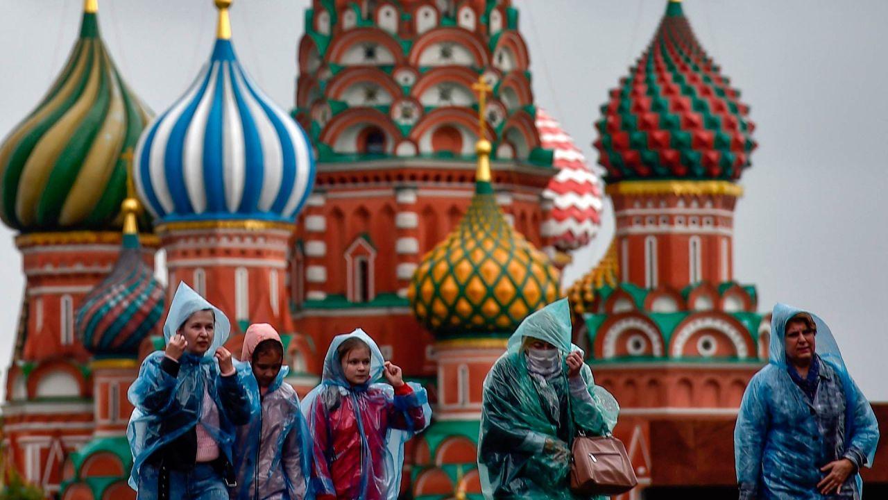 Personas con impermeables caminan por la Plaza Roja frente a la Catedral de San Basilio en un día lluvioso en Moscú. | Foto:Natalia Kolesnikova / AFP