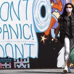 Una mujer vestida con una mascarilla pasa por un mural en el suburbio de Prahran en Melbourne. - Melbourne está experimentando reglas de bloqueo largas y duras mientras lucha contra una segunda ola del coronavirus Covid-19. | Foto:William West / AFP