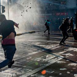 Un manifestante arroja piedras a un vehículo de la policía antidisturbios durante los enfrentamientos tras una protesta contra el gobierno del presidente chileno Sebastián Piñera en Santiago. | Foto:MARTIN BERNETTI / AFP