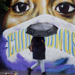 México, Tepetitla: una mujer con un paraguas pasa junto a una pintura mural que representa a una mujer con una máscara facial. | Foto:Jesús Alvarado / DPA