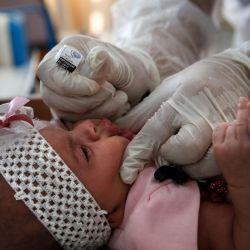 Un empleado de UNRWA proporciona la vacuna contra la poliomielitis y las vacunas contra el virus Rota para niños en una clínica en el campo de refugiados de Bureij en el centro de la Franja de Gaza. | Foto:MOHAMMED ABED / AFP
