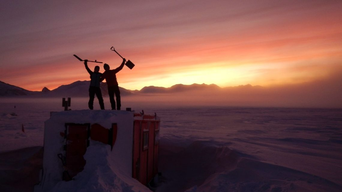 In this handout photo provided by British Antarctic Survey, field guides Sarah Crowsley, left, and Sam Hunt, right, pose for a photo after digging out the caboose, a container used for accommodation that can be moved by a tractor, at Adelaide island, in Antarctica on Friday, June 19, 2020.