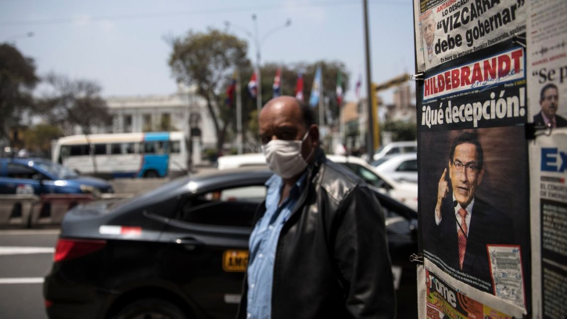 A man wearing a protective face mask due to the Covid-19 pandemic, walks past a newsstand displaying front-page headlines involving Peru's President Martin Vizcarra, outside Congress in Lima, Peru, Friday, September 11, 2020.