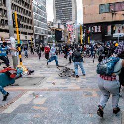 Manifestantes corren a cubrirse tras estallar enfrentamientos durante el quinto día consecutivo de protestas contra la brutalidad policial en Bogotá. | Foto:Juan Barreto / AFP