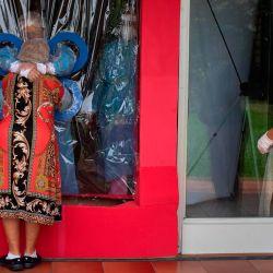 Yuri Cortez / AFP | Foto:María Hernández, de 38 años, (arriba, izquierda) abraza a su tía a través de una cortina transparente en un hogar de ancianos Hogar Jardín de Los Abuelitos mientras una enfermera los observa, en San Salvador, en medio de la nueva pandemia de coronavirus.