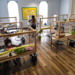 Un instructor recorre la sala mientras los estudiantes de diferentes escuelas y en diferentes grados siguen sus clases en línea desde escritorios separados por barreras de plástico en el Centro de Tutoría y Enriquecimiento Westwood STAR en Los Ángeles, California. | Foto:Robyn Beck / AFP