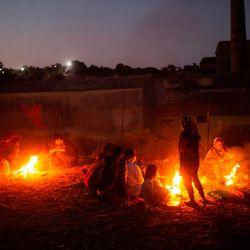 Refugiados y migrantes del campo destruido de Moria cocinan en llamas durante la tarde en la isla de Lesbos. | Foto:ANGELOS TZORTZINIS / AFP