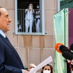 El personal médico toma fotos del ex primer ministro italiano Silvio Berlusconi mientras se dirige a los medios de comunicación, cuando abandona el Hospital San Raffaele en Milán después de que dio positivo en la prueba de coronavirus y estuvo hospitalizado. | Foto:Piero Cruciatti / AFP