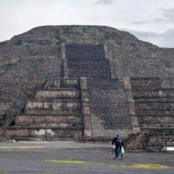 Un guardia en bicicleta patrulla el sitio arqueológico de Teotihuacan, una de las principales atracciones turísticas de México, durante su reapertura en medio de la pandemia del nuevo coronavirus COVID-19, en el municipio de Teotihuacan, Estado de México, México. | Foto:Claudio Cruz / AFP