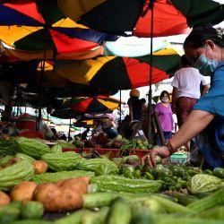 Una mujer compra verduras en un mercado de Phnom Penh.   Foto:TANG CHHIN Sothy / AFP