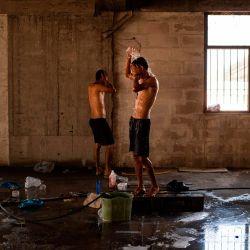 Los migrantes se limpian dentro de un edificio abandonado cerca del campamento de Kara Tepe en la isla de Lesbos.   Foto:ANGELOS TZORTZINIS / AFP