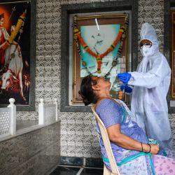 Un trabajador de salud recolecta una muestra de hisopo de un residente para la prueba de coronavirus Covid-19 en un templo en Mumbai.   Foto:Indranil Mukherjee / AFP
