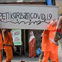 Los funcionarios locales llevan un ataúd simulado para promover la conciencia sobre el coronavirus COVID-19 en Yakarta.   Foto:BAY ISMOYO / AFP