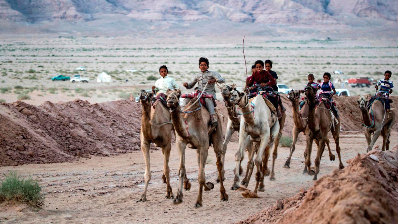 Camellos que llevan jinetes en la espalda, corren por una pista de tierra durante una carrera en el desierto del Sinaí del Sur de Egipto, después de más de seis meses de pausa debido al brote de coronavirus.   Foto:Khaled Desouki / AFP