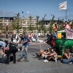 Los activistas del grupo Extinction Rebellion se dejan llevar por la policía mientras bloquean el tráfico en la plaza Kongens Nytorv en Copenhague, Dinamarca. | Foto:Emil Helms / Ritzau Scanpix / AFP