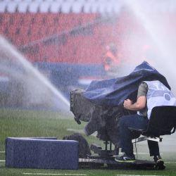 Un cameram se prepara para filmar mientras se sienta bajo dos chorros de riego para el césped antes del partido de fútbol francés L1 entre Paris Saint-Germain (PSG) y Metz, en el estadio Parc des Princes de París. | Foto:FRANCK FIFE / AFP