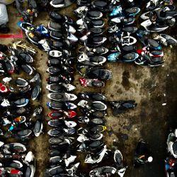 Una vista aérea muestra a un trabajador (abajo a la derecha) empujando una motocicleta retirada en una instalación de reciclaje de vehículos en la ciudad norteña de Taoyuan. | Foto:Sam Yeh / AFP