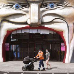 Una familia pasa por la entrada del Luna Park en el suburbio de St Kilda en Melbourne. - Melbourne continúa aplicando estrictas medidas de bloqueo para combatir una segunda ola del coronavirus Covid-19. | Foto:William West / AFP