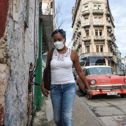 Una mujer con mascarilla contra la propagación del nuevo coronavirus, COVID-19, camina en La Habana. | Foto:Yamil Lage / AFP