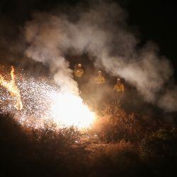 Los bomberos encienden una bengala para provocar un incendio en la espalda mientras trabajan para contener el incendio Bobcat que se quema en una ladera cerca de las casas en Monrovia, California. | Foto:Mario Tama / Getty Images / AFP