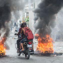 Personas en una motocicleta conducen a través de una barricada de llantas en llamas en la autopista Delmas en Puerto Príncipe. | Foto:Reginald LOUISSAINT JR / AFP