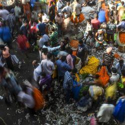 Los devotos hindúes y los vendedores de flores se reúnen en el principal mercado mayorista de flores de Calcuta. | Foto:Dibyangshu Sarkar / AFP