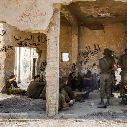 Los soldados israelíes se reúnen dentro de un antiguo edificio construido por Jordania durante un entrenamiento cerca de un campamento militar israelí en la aldea de Yatta en el sur de la Cisjordania ocupada. | Foto:HAZEM BADER / AFP