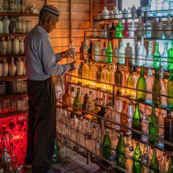 Esta fotografía muestra a Tengku Mohamad Ali Mansor inspeccionando una botella de vidrio en su museo de botellas en la aldea de Penarik en el distrito de Setiu del estado de Terengganu, en el este de Malasia. | Foto:Mohd Rasfan / AFP