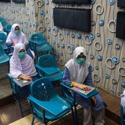 Los estudiantes que usan mascarillas asisten a una clase en una escuela en Karachi después de que los institutos educativos fueran reabiertos casi seis meses después de la propagación del coronavirus Covid-19. | Foto:Rizwan Tabassum / AFP