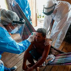 Trabajadores de salud del gobierno controlan la temperatura de un hombre en una comunidad ribereña del río Murutipucu en Igarape-Miri, Baixo Tocantins, estado de Pará, Brasil, para detectar casos de COVID-19 en medio de la población. | Foto:TARSO SARRAF / AFP