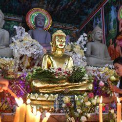 Una mujer coloca flores frente a las estatuas de Buda durante el festival Pchum Ben (Festival de la Muerte) en una pagoda en Phnom Penh. | Foto:TANG CHHIN Sothy / AFP