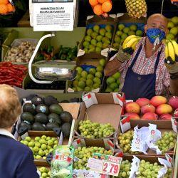 Un vendedor de frutas atiende a un cliente en el barrio de Vallecas en Madrid. | Foto:GABRIEL BOUYS / AFP