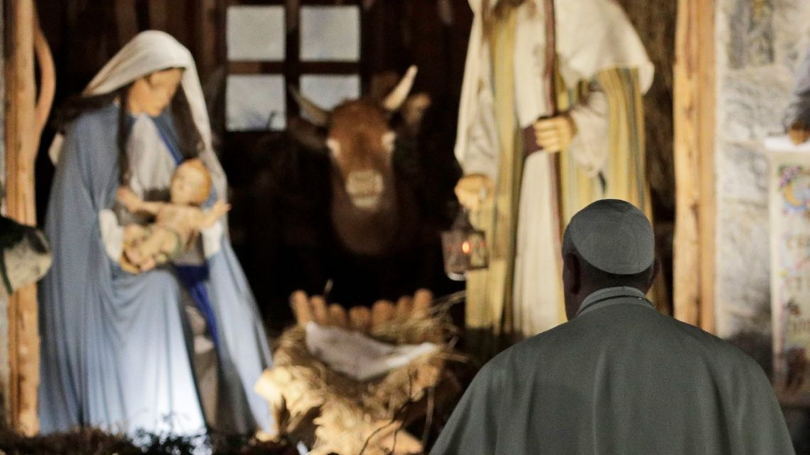 In this December 31, 2019 file photo, Pope Francis stops by the Nativity exposed in St. Peter's square after presiding over vespers of the Feast of St. Mary and Te Deum of Thanksgiving at year's end, in St. Peter's Basilica at the Vatican.
