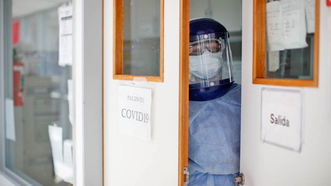 A doctor, dressed in full protective gear, looks out from an intensive care unit designated for COVID-19 patients.