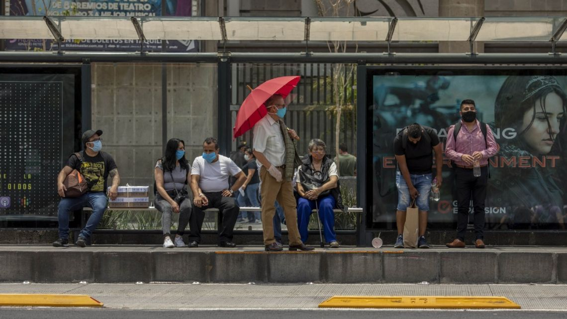 Commuters wearing protective masks wait for a bus in Mexico City.