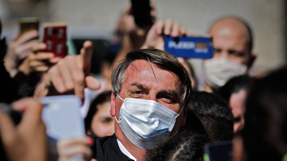 "Brazilian President Jair Bolsonaro gestures as he is surrounded by supporters while visiting the residence of an adviser in Brasília, on August 23, 2020. Bolsonaro on Sunday threatened to punch a reporter repeatedly in the mouth after being asked about his wife's links to an alleged corruption scheme. ""I so want to pound your mouth with punches,"" the far-right president said when a reporter from O Globo, posed the question."