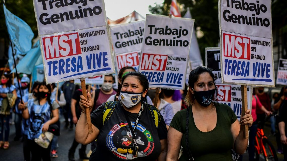 Members of leftist organisations hold signs during a protest against economic measures taken by the government in Buenos Aires on September 17, 2020.