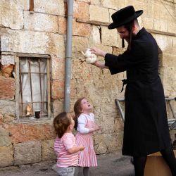 Un judío ultraortodoxo balancea un pollo sobre la cabeza de sus hijos mientras realiza la ceremonia Kapparot en el barrio ultraortodoxo de Mea Shearim en Jerusalén.   Foto:Emmanuel DUNAND / AFP