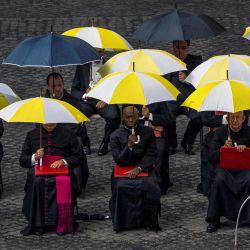 Los miembros del clero se sientan bajo su paraguas mientras asisten a la audiencia general semanal del Papa Francisco con un público limitado en el patio de San Damaso en el Vaticano en medio de la pandemia de Covid-19.   Foto:Tiziana Fabi / AFP