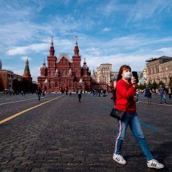 Una mujer con una mascarilla para protegerse contra la enfermedad del coronavirus camina por la Plaza Roja en el centro de Moscú.   Foto:Yuri Kadobnov / AFP